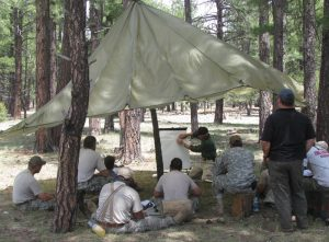 An Army group sitting under a parachute studying outdoor survival techniques.